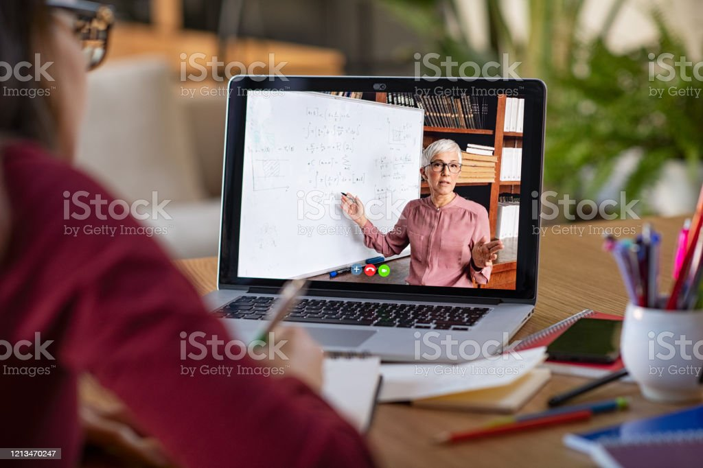 Studying with video online lesson at home Young student watching lesson online and studying from home. Young woman taking notes while looking at computer screen following professor doing math on video call. Latin girl student studying from home and watching teacher explaining math formula on video chat. Adult Stock Photo