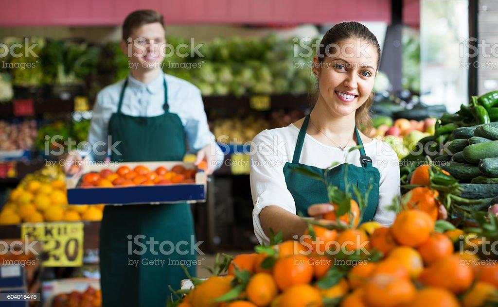 Stuff in apron selling sweet oranges, lemons and tangerines stock photo
