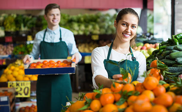 Stuff in apron selling sweet oranges, lemons and tangerines smiling european stuff in apron selling sweet oranges, lemons and tangerines market vendor stock pictures, royalty-free photos & images