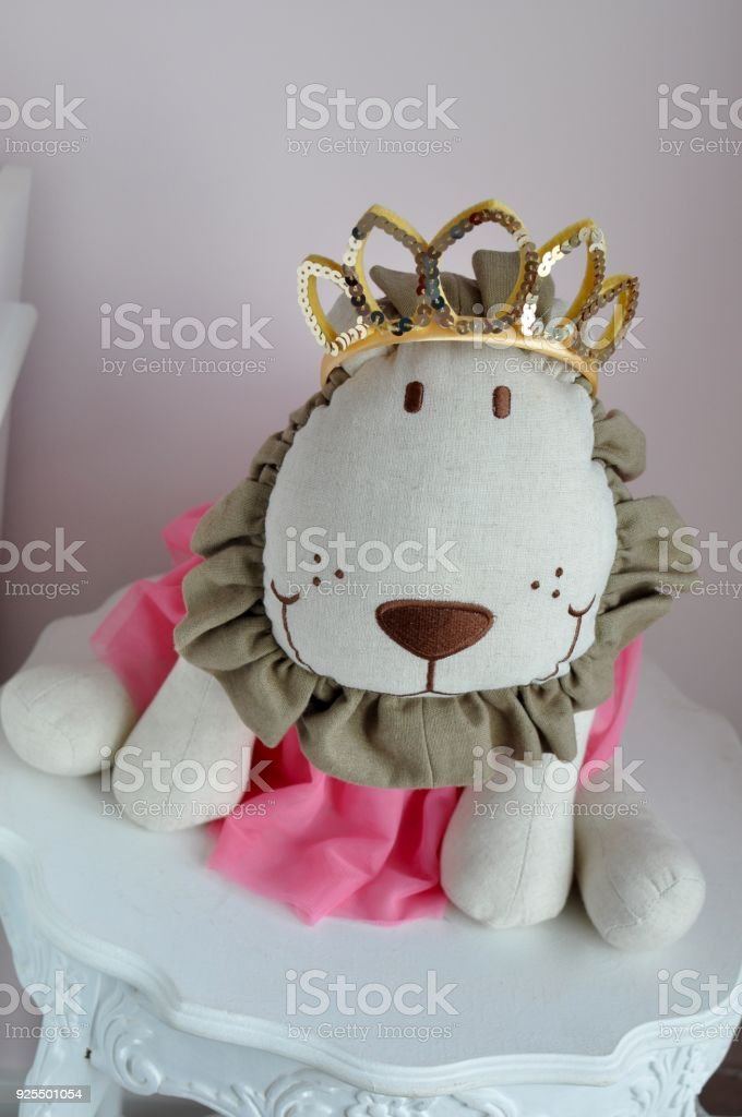Close-up of lion stuffed animal with crown and tutu in baby nursery...