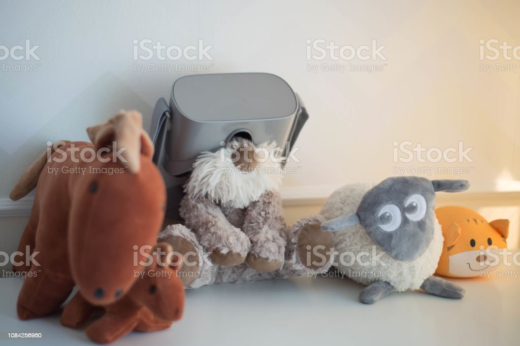 Stuffed animal wearing virtual reality glasses along with other toy...