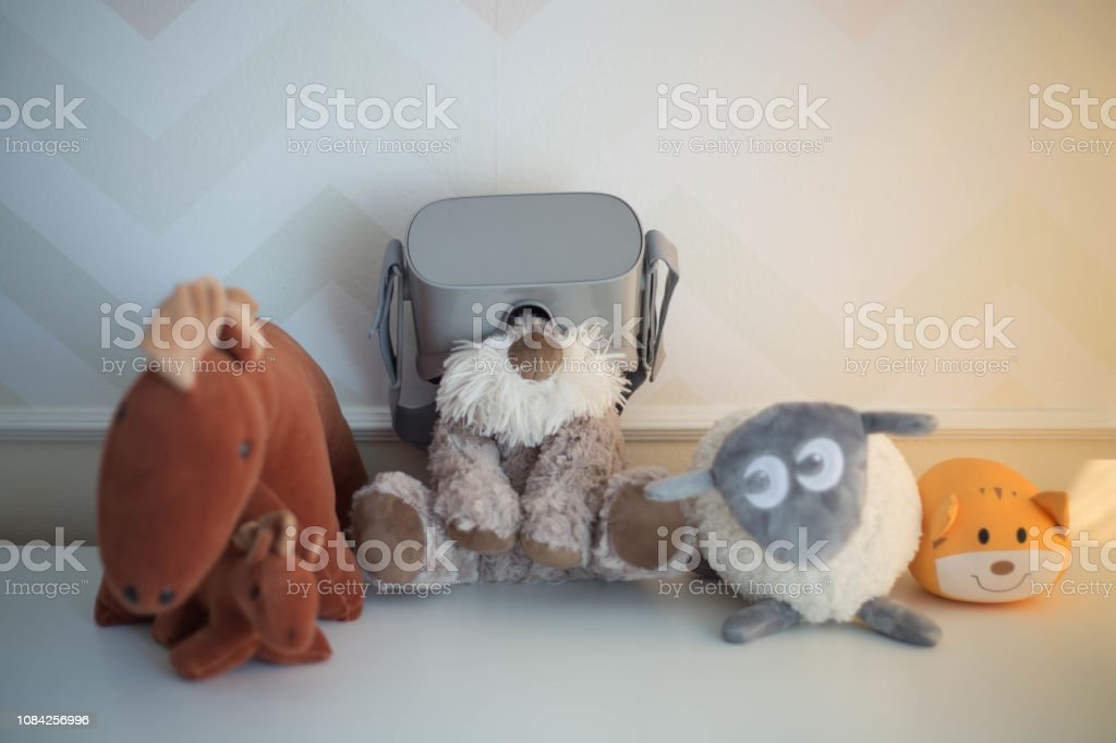 Stuffed animal wearing virtual reality glasses along with other toy animals. stock photo