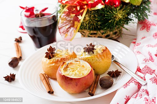 istock Stuffed baked apples with cottage cheese, raisins and almonds for Christmas on a white background. Xmas food dessert. 1049184522