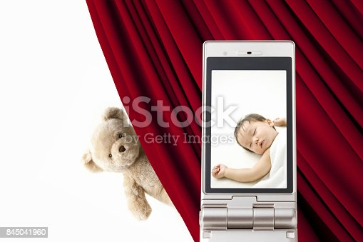 istock Stuffed bears and baby pictures on the mobile screen 845041960
