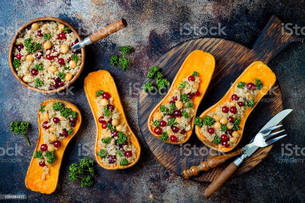Abóbora recheada com grão de bico, cranberries, quinoa cozida em noz-moscada, cravo, canela. Receita do jantar de ação de Graças. Vegan saudável sazonal queda ou comida de outono - foto de acervo