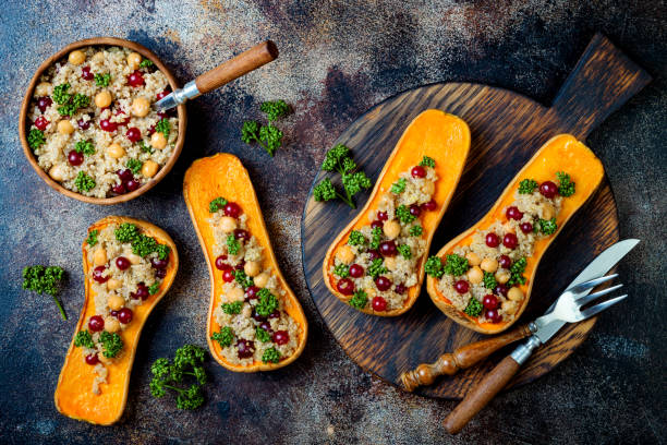 stuffed butternut squash with chickpeas, cranberries, quinoa cooked in nutmeg, cloves, cinnamon. thanksgiving dinner recipe. vegan healthy seasonal fall or autumn food - vegetariano foto e immagini stock