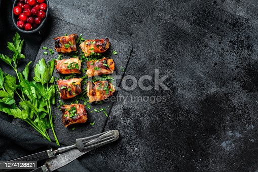 stuffed chicken breasts, fillets rolled in bacon. Black background. Top view. Copy space.