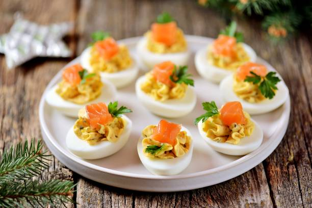 Stuffed chicken eggs with soft cheese, capers and salted salmon. stock photo