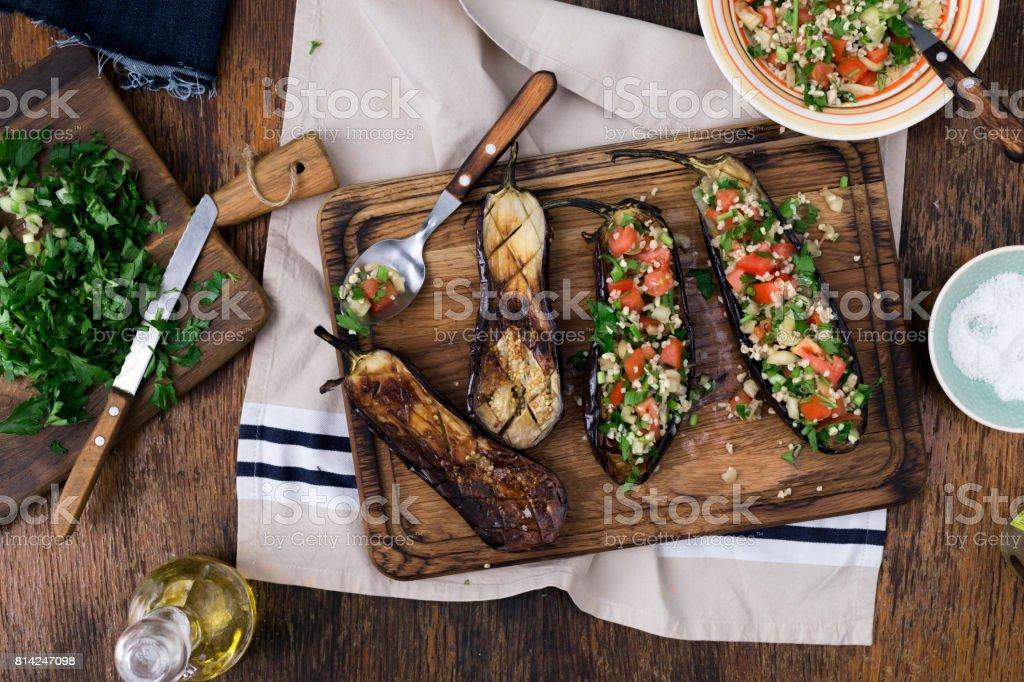 Mingau de berinjela recheadas bulgur e legumes numa tábua. Conceito de comida saudável de cozinhar - foto de acervo