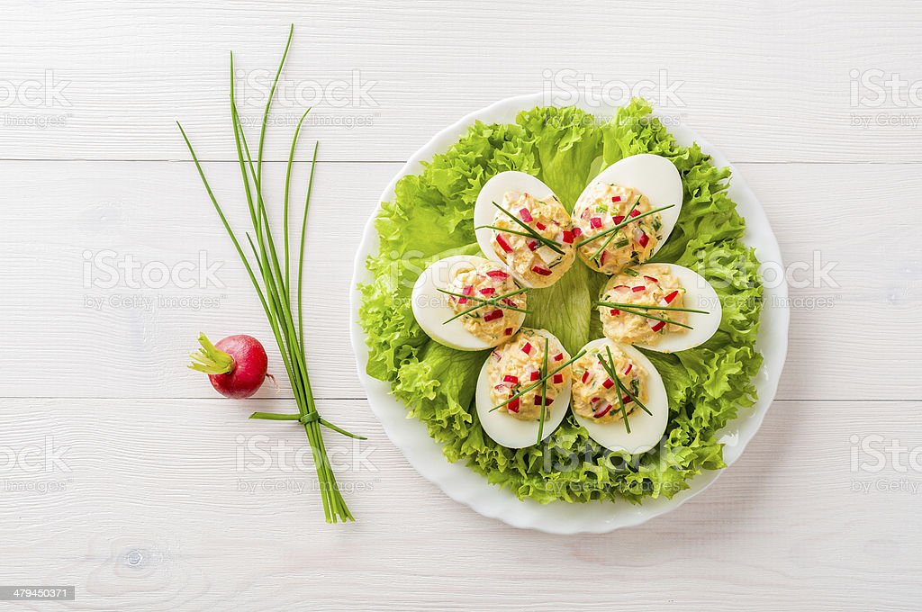 Stuffed eggs on lettuce with chives garnish stock photo