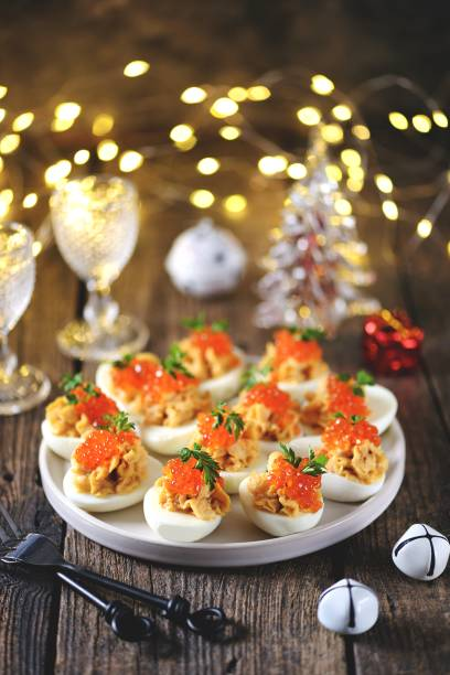 Stuffed eggs with salmon caviar. Christmas background. stock photo