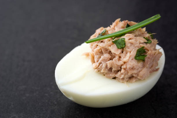 Stuffed eggs with tuna Stuffed eggs with tuna on black stone background tuna seafood stock pictures, royalty-free photos & images
