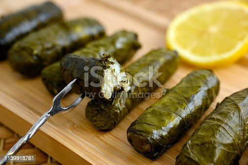 Delicious stuffed grape leaves (the traditional dolma of the mediterranean cuisine) on wooden tray with lemon slice
