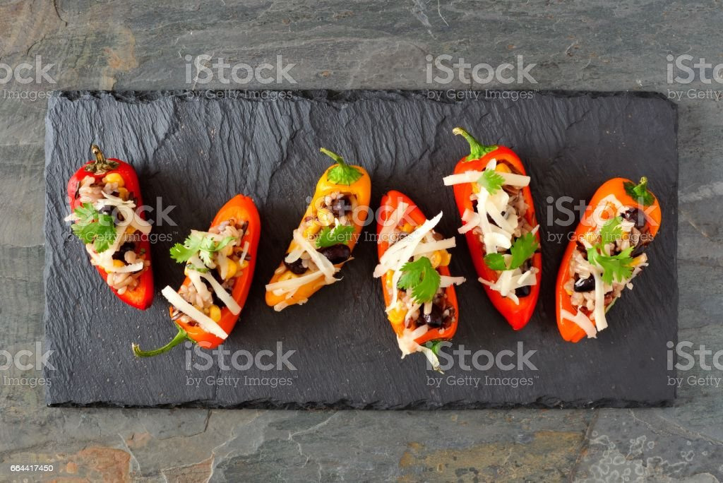 Stuffed mini peppers, above view on a slate background stock photo