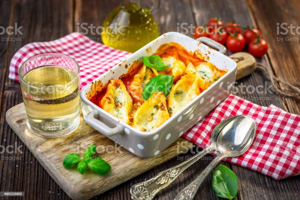 Stuffed pasta shells casserole with gorgonzola, ricotta and tomato sauce stock photo