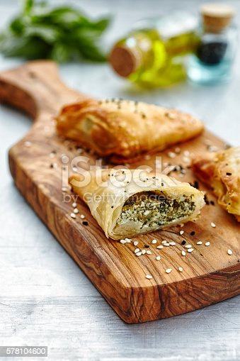 Stuffed pastry on wooden cutting board and oil bottles in the background