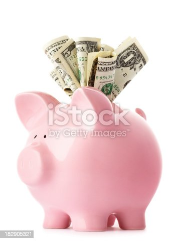 Savings - pink piggy bank with US dollars.