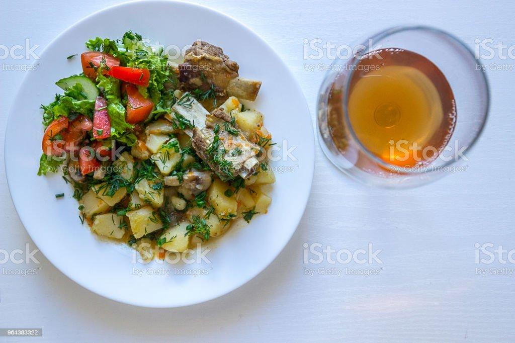 Gevulde aardappelen met kalfsvlees ribben, frisse salade en glas roze wijnstokken - Royalty-free Avondmaaltijd Stockfoto