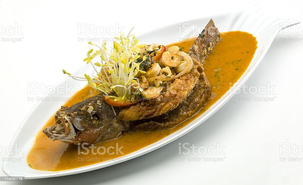 Stuffed Crispy Red Snapper with coconut rice and seafood on white...