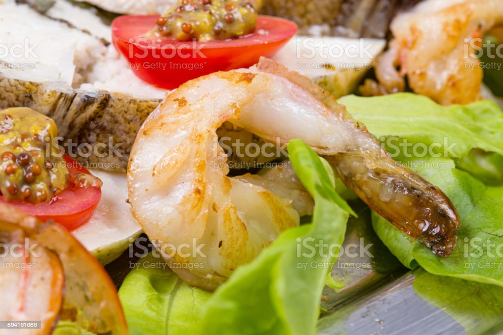 Stuffed seabass with fried shrimp and salad royalty-free stock photo
