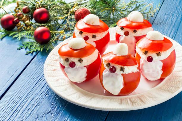 gefüllte tomaten in form von weihnachtsmann für weihnachten - weihnachtsessen ideen stock-fotos und bilder