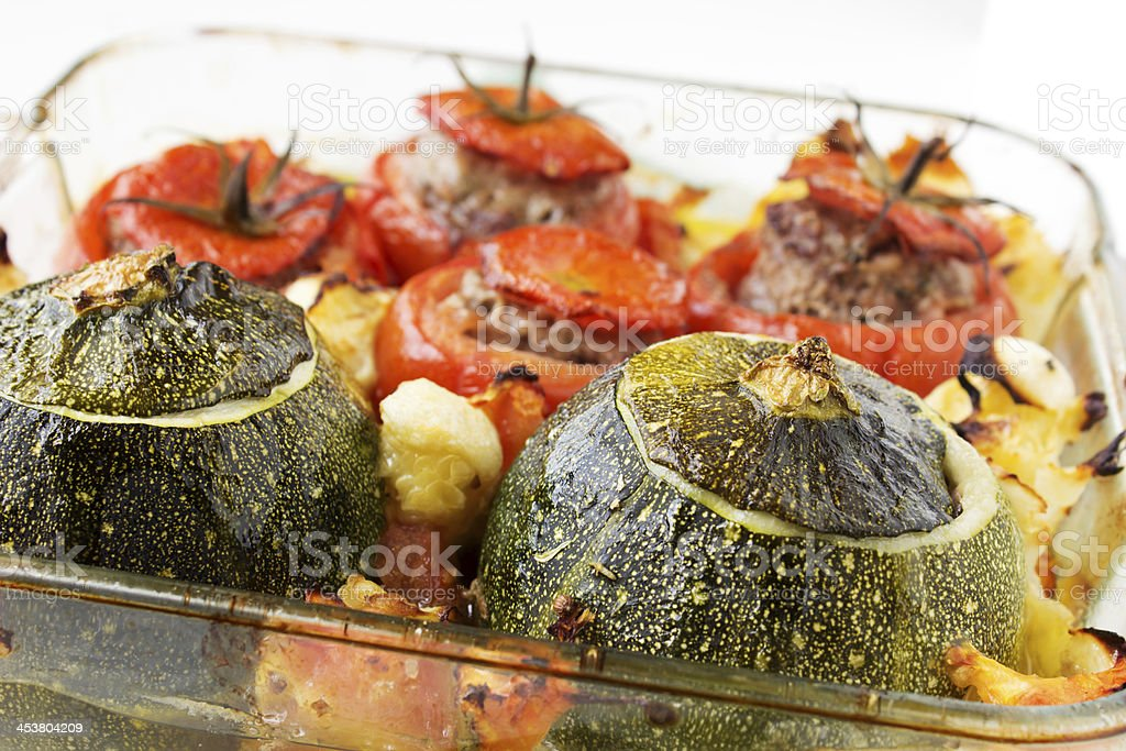 Transparent plate with cooked tomatoes and marrows stuffed with...