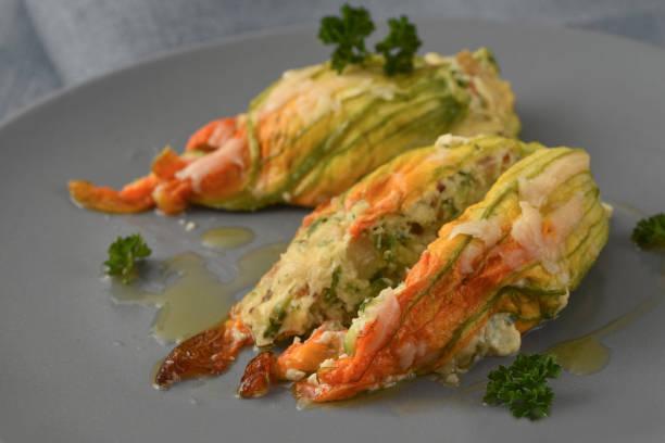 gefüllte zucchini oder zucchini-blüten mit parmesan-käse und petersilie garniert auf einer grauen platte gebacken - gefüllte zucchini vegetarisch stock-fotos und bilder