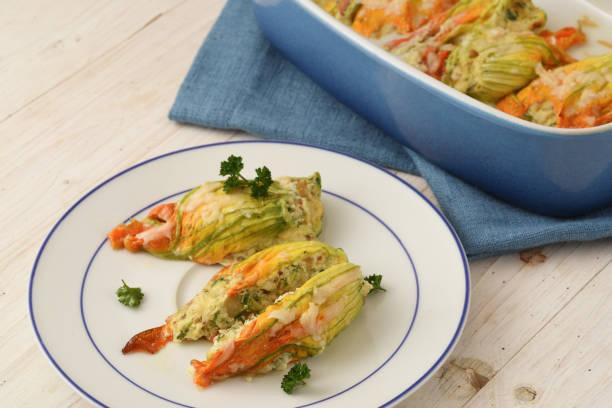 gefüllte zucchini oder zucchini-blüten, überbacken mit parmesan-käse und petersilie garniert auf einer platte und in eine kasserolle, blau weiße serviette holztisch - gefüllte zucchini vegetarisch stock-fotos und bilder