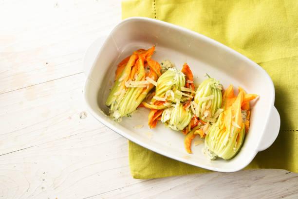 gefüllte zucchini oder zucchini-blüten in einem topf auf einem weißen holztisch mit einer grünen serviette, große textfreiraum, draufsicht von oben - gefüllte zucchini vegetarisch stock-fotos und bilder