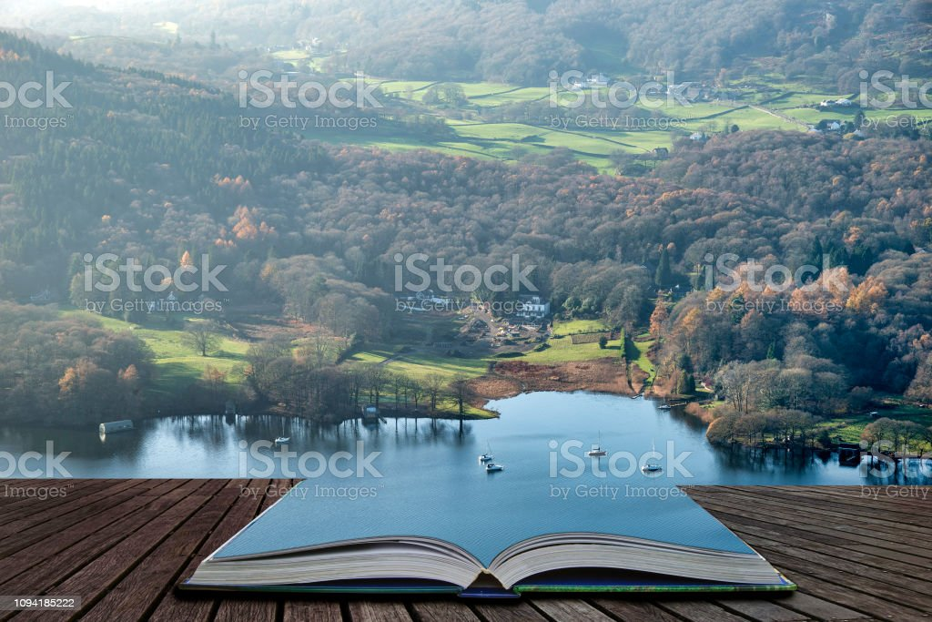 Stuning vibrant Autumn Fall landscape image of view from Gummers How down onto Derwent Wter in Lake District coming out of pages of open story book stock photo