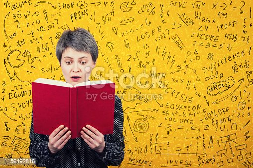 istock Stunned woman reader looking amazed in a book. Mathematics calculations, economics formula and equations difficult to solve. Ideas and planning concept. 1156492816