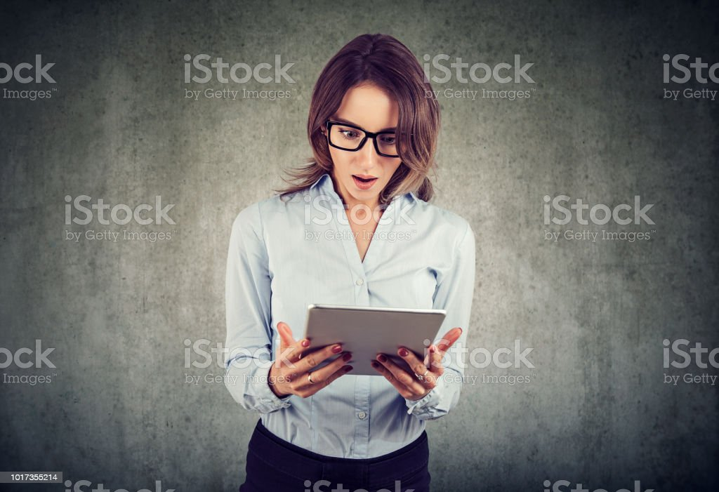 stunned woman, surprised with wide open mouth, shocked by what she sees on her tablet stock photo