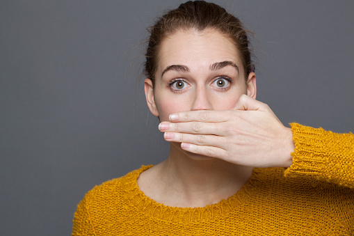 Stunned Young Woman Covering Her Mouth For Silence Stock Photo - Download Image Now