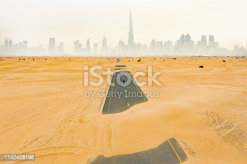 istock Stunning aerial view of an unidentified person walking on a deserted road covered by sand dunes in Dubai desert. Dubai skyline surrounded by fog in the background. Dubai, United Arab Emirates. 1142428195