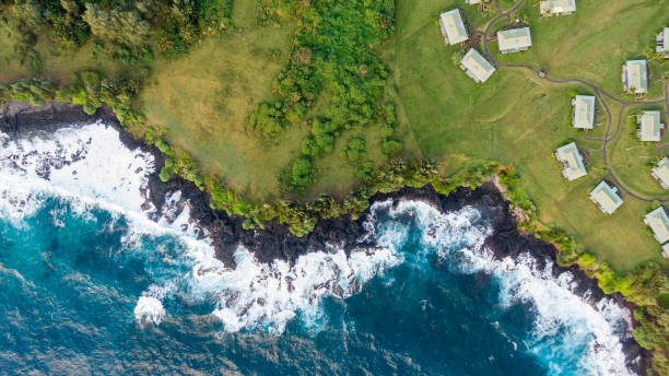 stunning aerial view of the rough volcanic coastline in the town of hana on the eastern side of the island of maui, hawaii. beautiful waves, volcanic rocks, grassland, trees and bungalow houses. - hawaii home stock photos and pictures