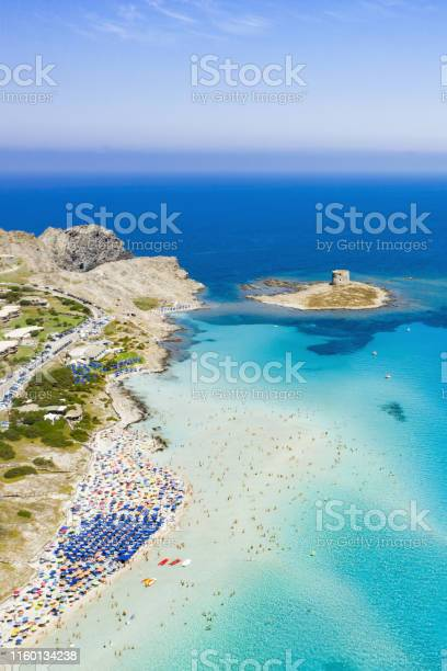 Photo of Stunning aerial view of the Spiaggia Della Pelosa (Pelosa Beach) full of colored beach umbrellas and people sunbathing and swimming in a beautiful turquoise clear water. Stintino, Sardinia, Italy.
