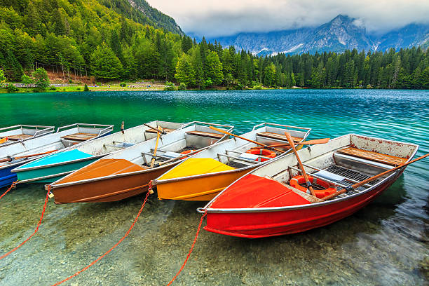 Stunning alpine landscape and colorful boats,Lake Fusine,Italy,Europe stock photo