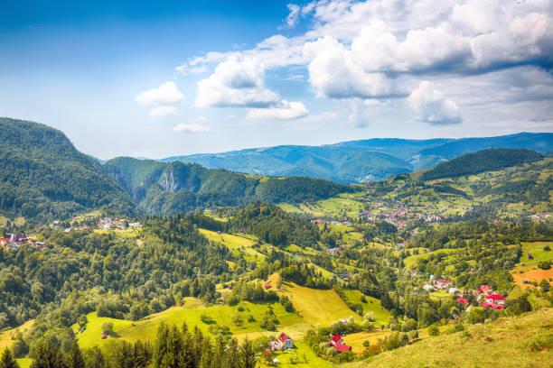 Stunning alpine landscape with green fields and Piatra Craiului mountains in Dambovicioara Commune stock photo
