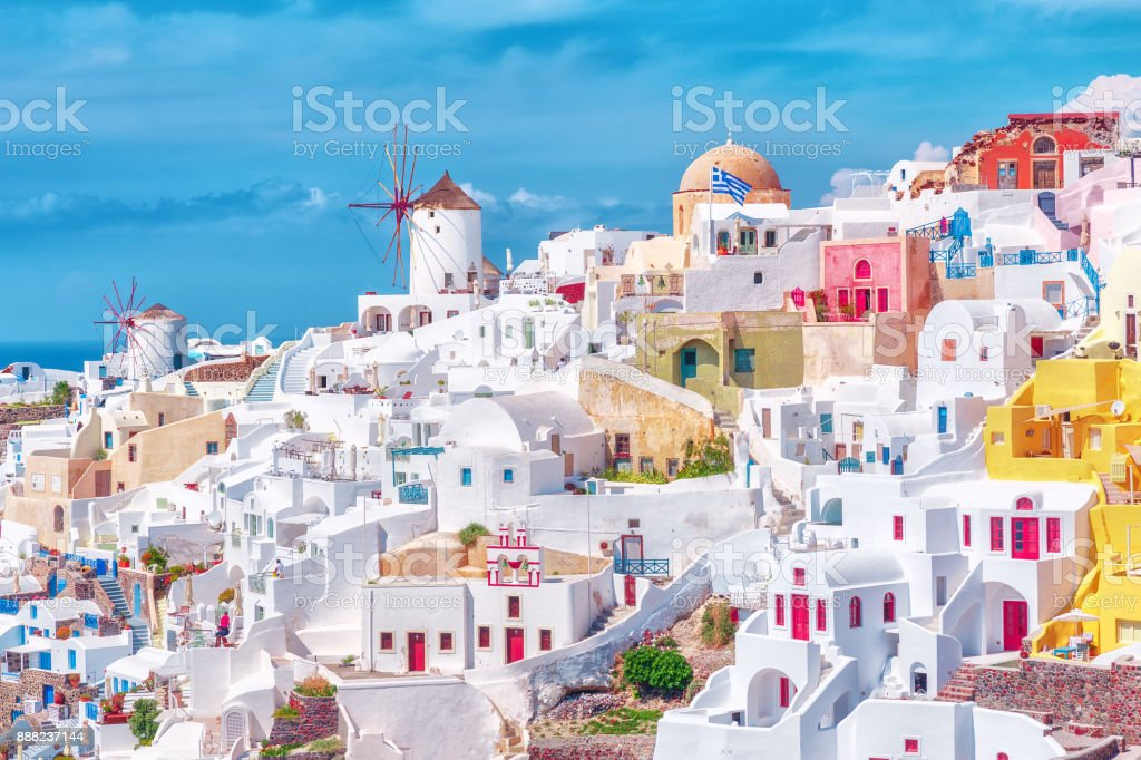 Stunning, amazing and beautiful classic white and caramel  color Greek architecture with unbelievable wind mills on Santorini volcano Cyclades Caldera island in warm waters of Aegean sea in Greece. stock photo