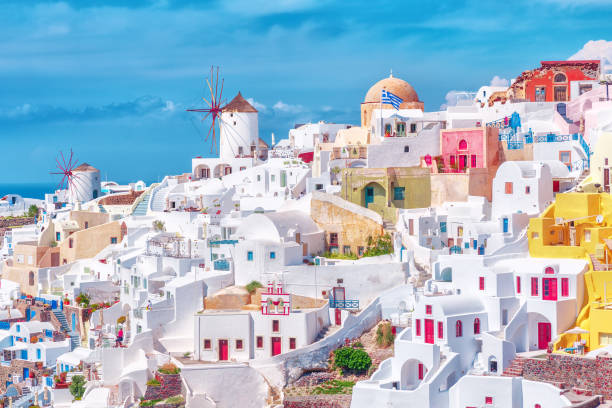 stunning, amazing and beautiful classic white and caramel  color greek architecture with unbelievable wind mills on santorini volcano cyclades caldera island in warm waters of aegean sea in greece. - santorini stock photos and pictures