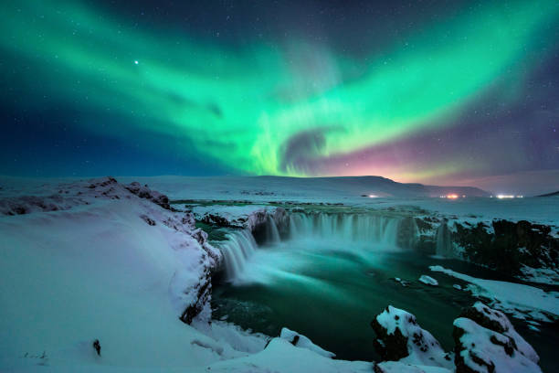 a stunning aurora shape like phoenix bird appears above the landscape of godafoss water fall in winter iceland - aurora boreale foto e immagini stock