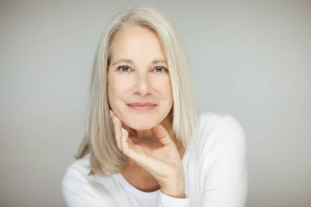 stunning beautiful and self confident best aged woman with grey hair stunning beautiful and self confident best aged woman with grey hair smiling into camera, portrait with white background 60 64 years stock pictures, royalty-free photos & images