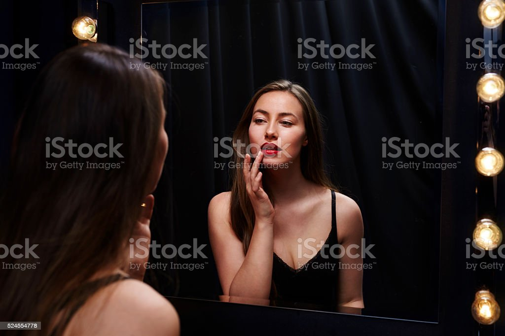Stunning beauty touching at lipstick in mirror's reflection stock photo