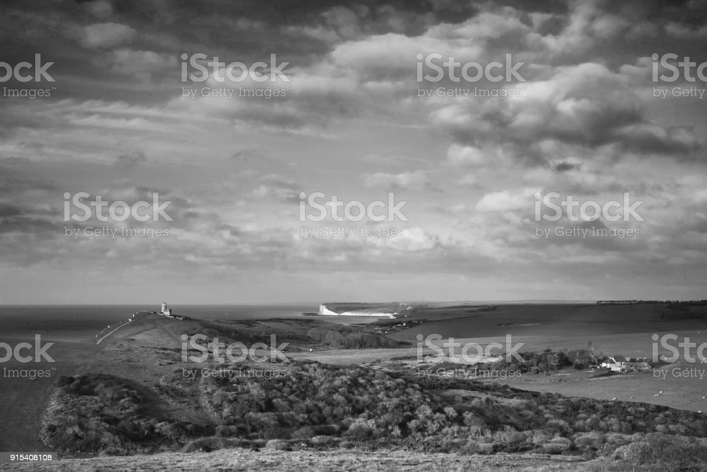 Stunning black and white landscape image of Belle Tout lighthouse on South Downs National Park during stormy sky stock photo