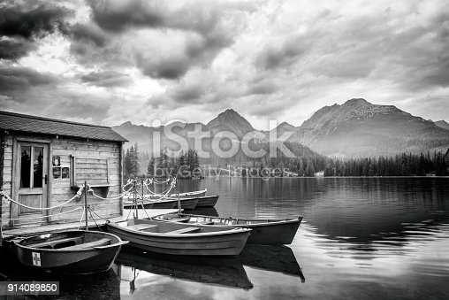 istock Stunning black and white landscape with cloudy sky, mountains and lake with pleasure boats, Strbske pleso, High Tatras, Slovakia 914089850