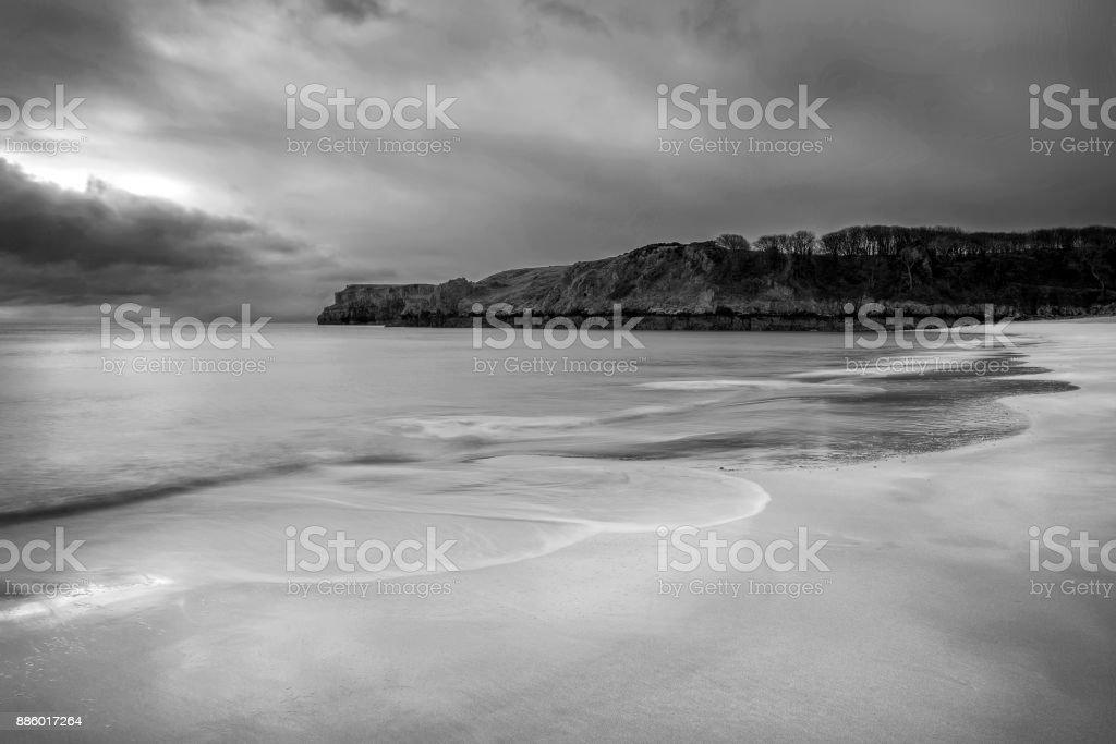 Stunning black and white sunrise landscape image of Barafundle Bay on Pembrokeshire Coast in Wales stock photo
