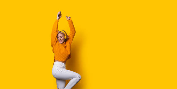Stunning blonde caucasian girl dressed in an orange sweater and white jeans is dancing while posing on a yellow background and listening to music stock photo