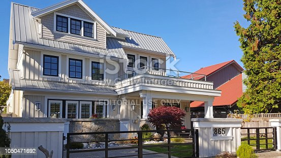 Crescent Beach,British Columbia,Canada- October 6,2018:  Exterior view of White and grey board and batten three story home. Autumn season with red Japanese maple tree. Lots of windows with shutters.  Metal gate in front.