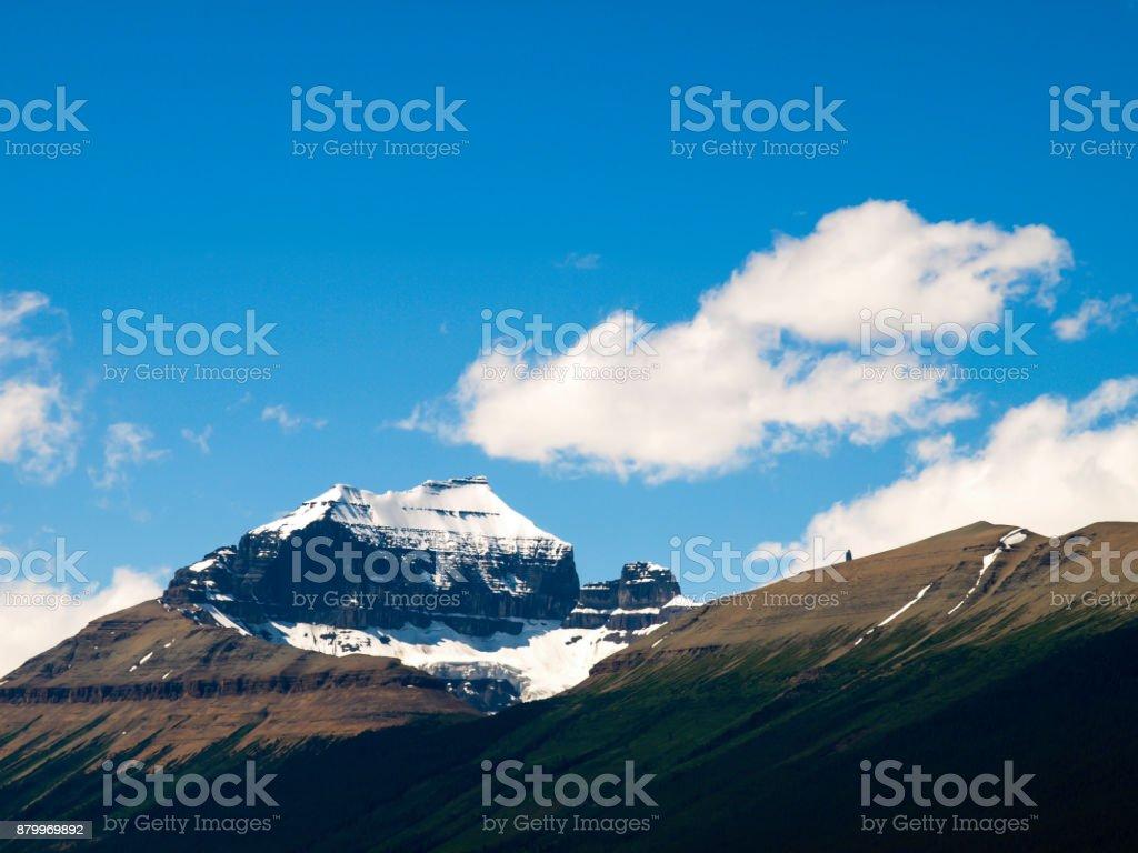 Stunning bring mountain peak showing details of snowy glacier on peak and smooth rocky sides with lush green forest below. Taken on Hghway 93 between Jasper adn Banff stock photo