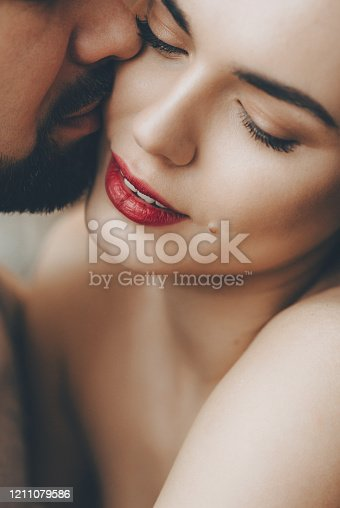 956369394 istock photo Stunning caucasian girl with red lips is kissed by her bearded lover while embracing each other 1211079586